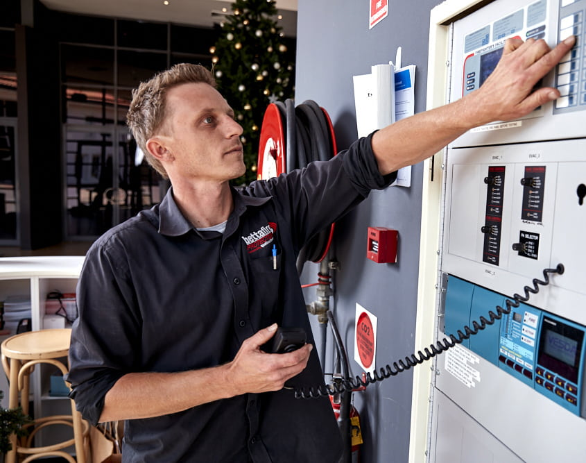 Accredited CFSP technician from Betta Fire Protection conducting a fire alarm inspection and fire detection system maintenance.